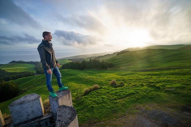 自由を楽しんで祝う夕焼け空を見上げる成功した男。人生の知覚の成功、心の安らぎの概念を感じるポジティブな人間の感情。無料の幸せな男