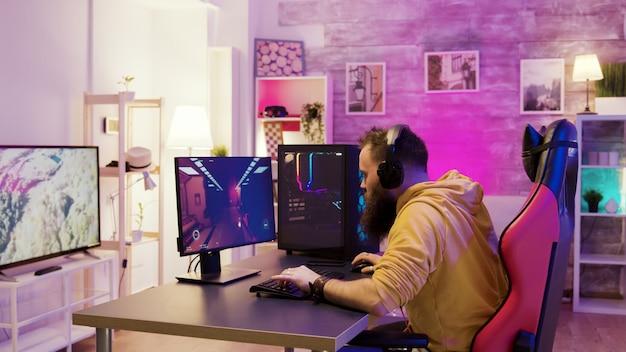 화려한 네온이 있는 방에서 온라인 비디오 게임을 하는 성공한 남자. 게임의 자에 앉아 남자입니다.