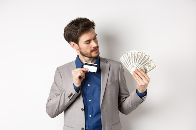 성공적인 남자 플라스틱 신용 카드를 표시 하 고 달러 지폐 팬을보고, 돈을 입금, 흰색 바탕에 서 서.