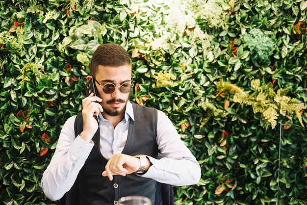 Successful man talking on phone checking time