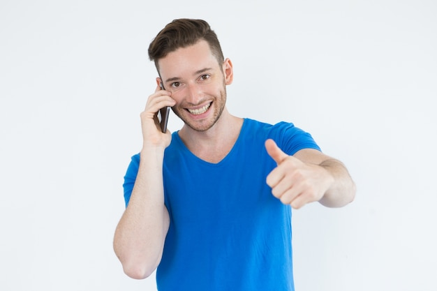 Successful man using phone and showing thumb-up