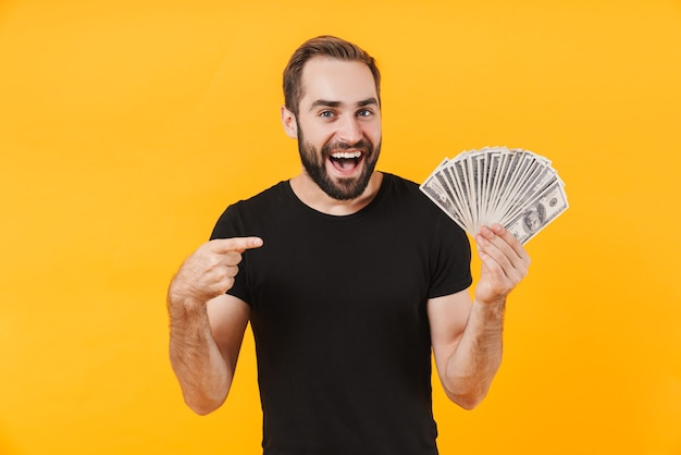 Successful man wearing basic black t-shirt smiling and holding money cash isolated over yellow wall