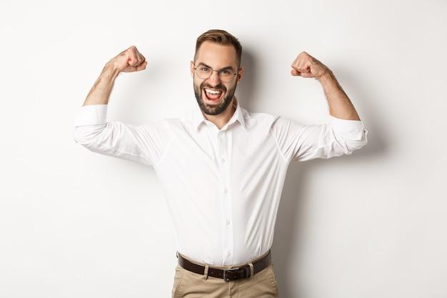 성공적인 매니저 플렉스 팔뚝, 근육을 보여주고 자신감을 보이며 흰색 배경 위에 서 있습니다.