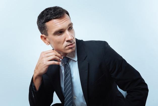 成功したマネージャー。椅子に座って、成功したマネージャーでありながら脇を見ているハンサムな素敵な楽しい男