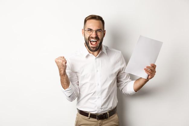 Manager di successo che fa la pompa del pugno, gioia del lavoro e mostra documenti, in piedi su sfondo bianco, caso vincente.