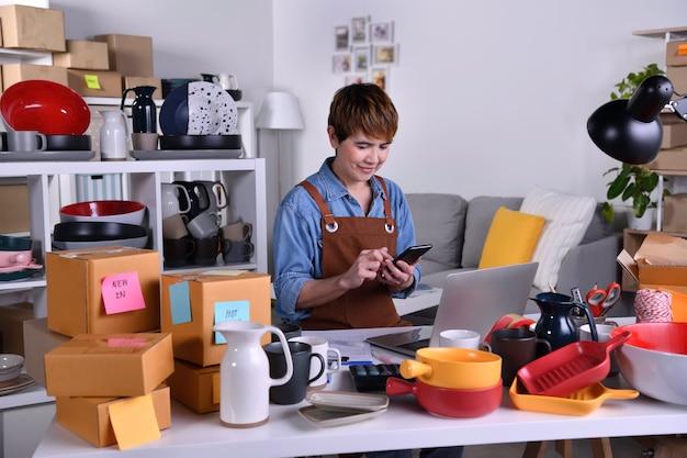 성공적인 성숙한 아시아 여성 기업가, 비즈니스 소유자는 스마트폰에서 온라인 주문을 보면서 행복해합니다. 가정 개념에서 온라인 판매 비즈니스 작업