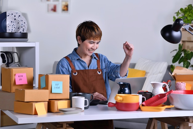 성공적인 성숙한 아시아 여성 기업가, 점토 세라믹 제품으로 홈 오피스에서 일하는 노트북 컴퓨터를 보면서 팔을 들고 있는 비즈니스 소유자