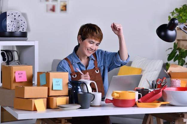 성공한 성숙한 아시아 여성 기업가, 점토 세라믹 제품으로 홈 오피스에서 일하는 노트북 컴퓨터를 보면서 팔짱을 낀 사업가