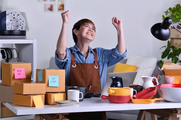 성공적인 성숙한 아시아 여성 기업가, 그녀의 점토 세라믹 제품으로 홈 오피스에서 랩톱 컴퓨터를 사용하면서 팔짱을 끼고 있는 비즈니스 소유자