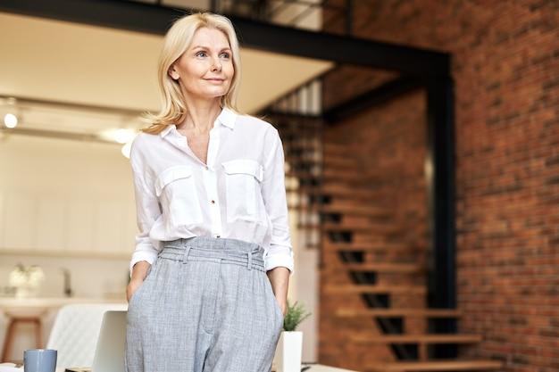 上のオフィスに立ってポーズをとっている間脇を見て成功した成熟した金髪のビジネス女性
