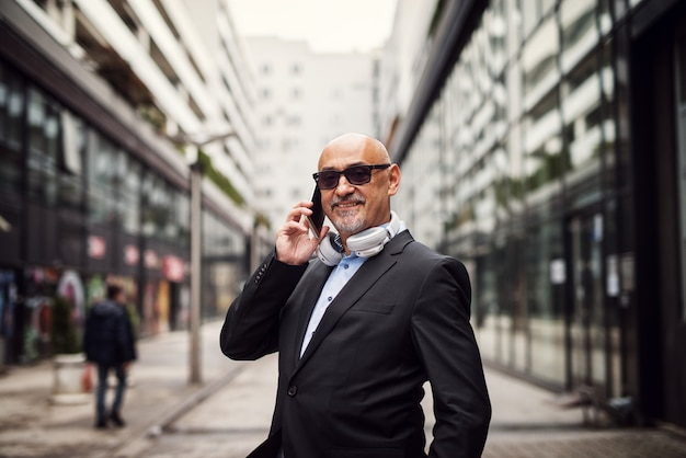 Successful mature businessman is making a call on a street.