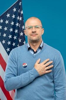 Успешный зрелый бизнесмен держит правую руку на груди, стоя перед камерой на фоне американского флага и синего цвета
