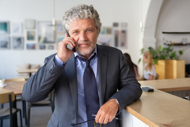 Successful mature businessman talking on mobile phone, standing at co-working, leaning on desk, looking at camera a