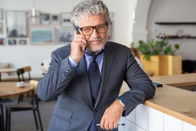 眼鏡をかけ、携帯電話で話し、コワーキングに立って、机に寄りかかって、カメラを見て成功した成熟したビジネスマン