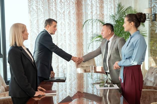Успешные зрелые бизнесмены или делегаты в официальной одежде приветствуют друг друга рукопожатием за столом после переговоров и заключения сделки