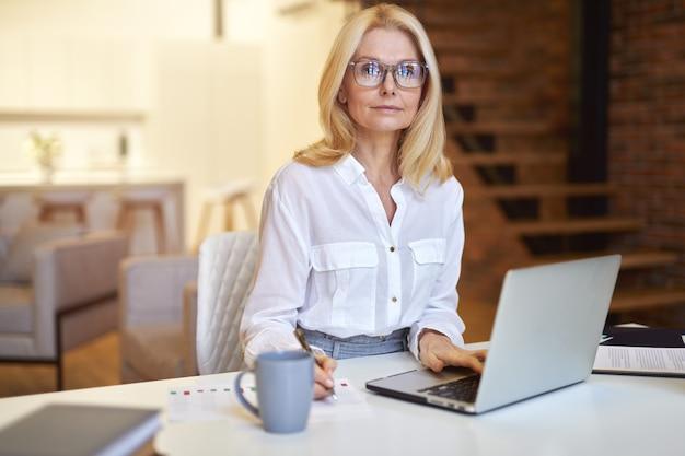 안경을 쓰고 노트북을 사용하여 카메라를 보고 있는 성공적인 성숙한 여성 사업가