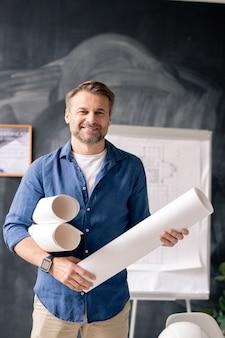 ホワイトボードの背景にカメラの前に立って圧延の青写真と成功した成熟したエンジニア