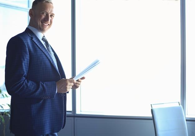 成功した成熟した起業家は、注意深く集中した外観でドキュメントを研究しています。