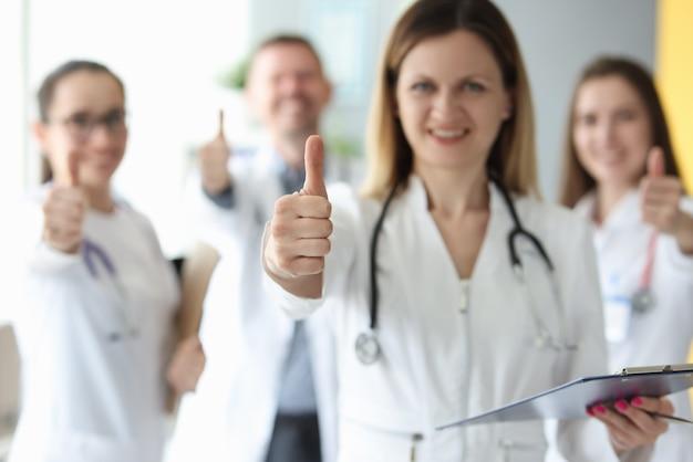 Успешная медицинская бригада в белых халатах показывает палец вверх
