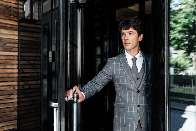 Успешный бизнесмен средних лет в костюме покидает