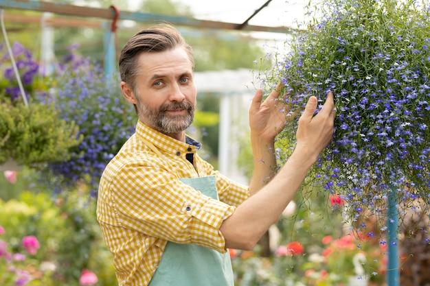 小さな花が咲き、温室の中に立っているエプロンで成功した中年の庭師