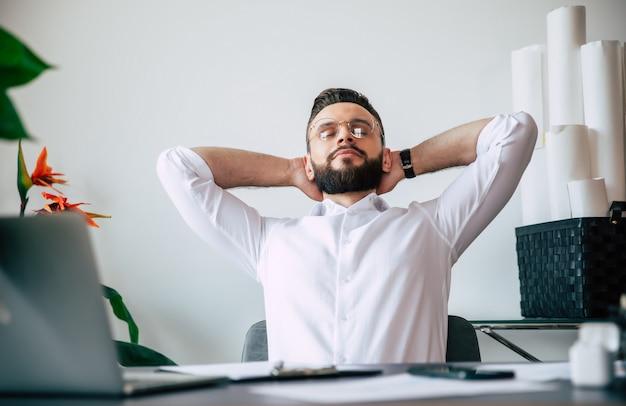 Успешный современный бородатый офисный мужчина отдыхает после тяжелой и хорошей работы за своим рабочим столом