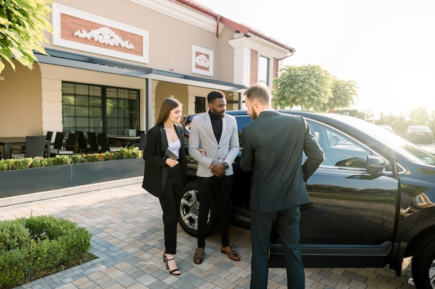 Successful multiethnical business people standing outdoors on the territory of car dealership. young man manager showing the car to the couple, african guy and caucasian girl. sale or rent of cars