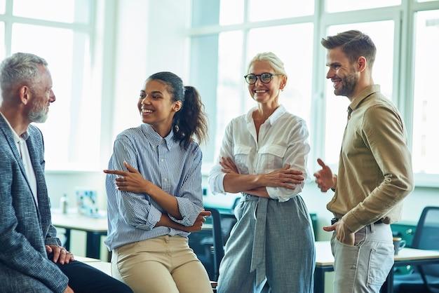 現代のオフィスに立ってコミュニケーションと議論を行う成功した多民族ビジネスチーム