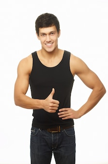 Successful muscled young man showing thumb up and smiling