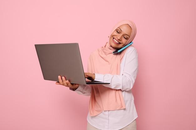 히잡을 쓴 성공적인 이슬람 아랍 여성, 휴대전화로 비즈니스 스마트 캐주얼 대화를 하고, 노트북에 텍스트를 입력하는 동안 모니터 화면을 보며 미소를 짓습니다. 공간 복사, 분홍색 배경