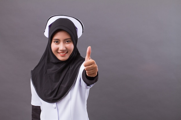 Successful muslim nurse giving thumb up