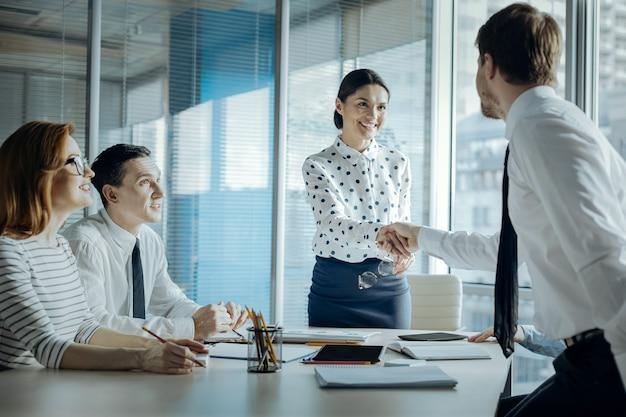 成功した交渉。オフィスで彼と彼女の従業員との会議をしながら彼女のビジネスパートナーの1つに握手を与える美しい若い実業家