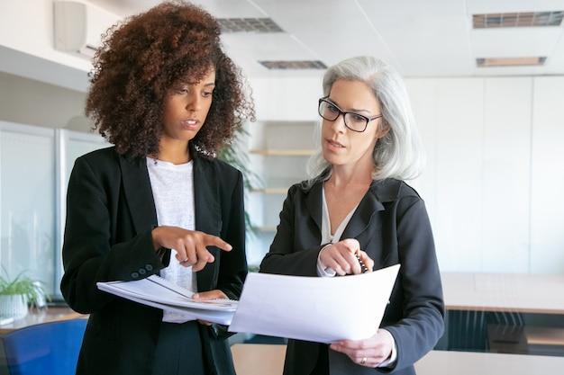 分析データを一緒に比較する成功したオフィスの雇用主。会議室でドキュメントやレポートを指して自信を持って女性マネージャーに焦点を当てた。チームワーク、ビジネス、管理の概念