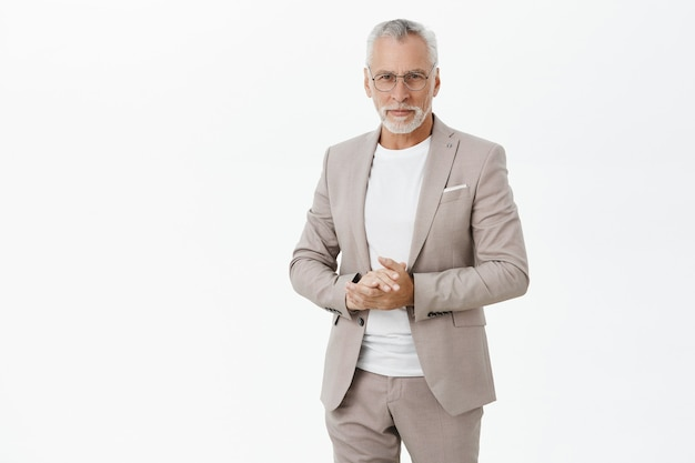 自信を持って見えるスーツとメガネで成功した老人実業家