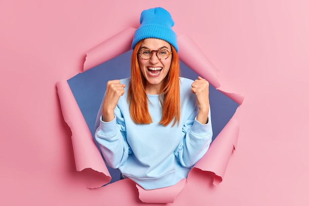 成功した楽観的な赤毛の女性は握りこぶしを上げ、イエスのジェスチャーをし、青い服を着て喜びで勝利の叫びを祝います。