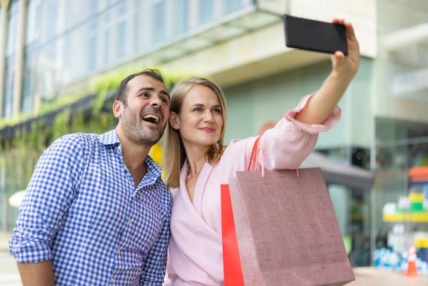 成功した個人的な買い物客は、幸せなクライアントと自己肖像画を取っている。