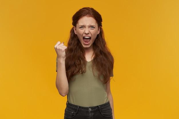 긴 생강 머리를 가진 성공적이고 긍정적 인 여성. 녹색 티셔츠를 입고. 사람과 감정 개념. 주먹을 들고 축하의 소리를 지르십시오. 오렌지 벽 위에 절연