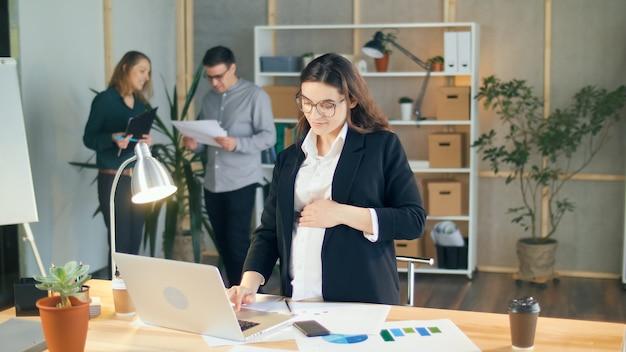 成功した妊娠中の実業家は、快適でモダンなオフィスで同僚と協力しています。ラップトップに取り組んでいる幸せな妊娠中の女性、優しく彼女の腹を撫でます。仕事、実業家、そして母性。