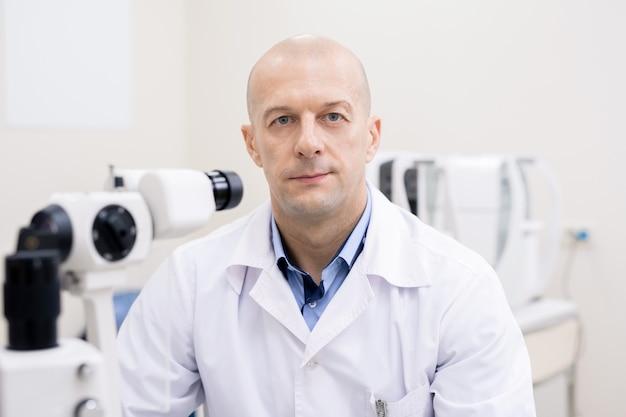 Успешный профессионал в белом халате, работающий с новым медицинским оборудованием