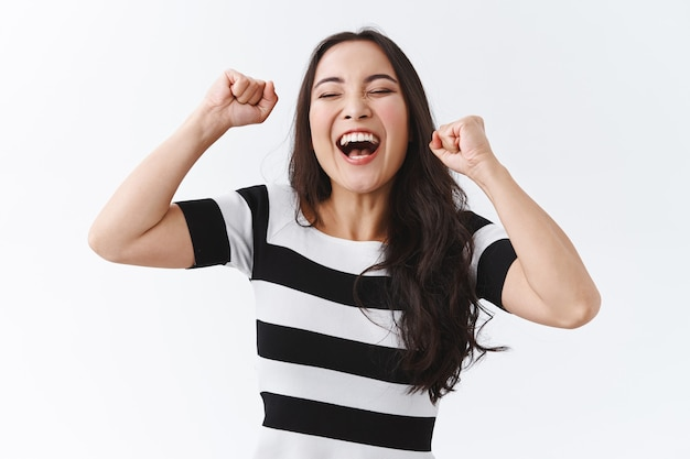 Successful, relieved young happy asian woman in striped t-shirt lifting hands up, fist pump like champion, feel lucky and upbeat as winning, triumphing yelling yeah, celebrating victory