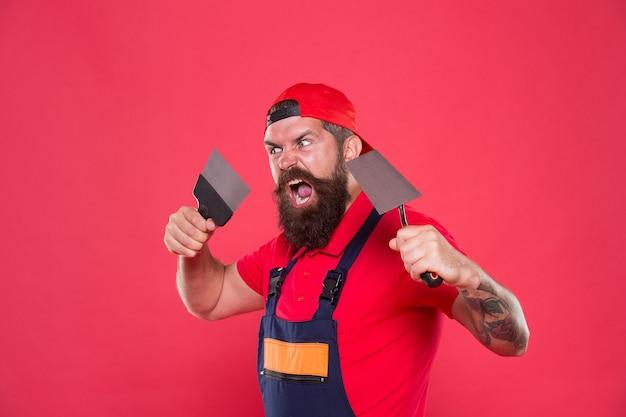 성공적인 리노베이션. 석고 도구와 수염된 남자 노동자입니다. 모자 빨간색 배경에 석고 소식통 작성기입니다. 인테리어 디자이너. 전문 미장공. 숙련된 미장공. 수리 성공.