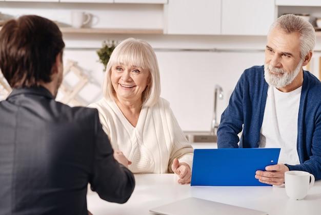 会話の成功した結果。家に座って握手しながら弁護士と合意について話し合う喜んで陽気な笑顔の老夫婦