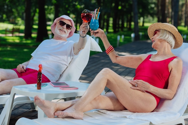 Successful retired man and woman feeling relaxed while chilling near outside pool