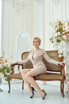 Successful rich woman without complexes on weight poses at home. young pensioner, business woman