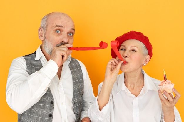 Successful romantic senior couple celebrating marriage anniversary. studio shot of handsome elderly man and mature female in red bonnet blowing whistles, having fun, eating birthday cupcake