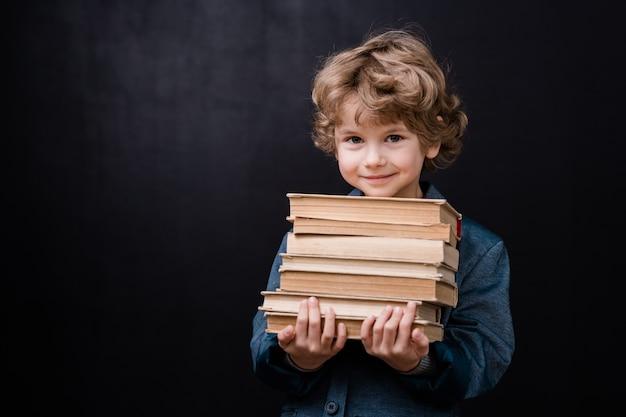 Успешный школьник держит стопку книг против черного пространства