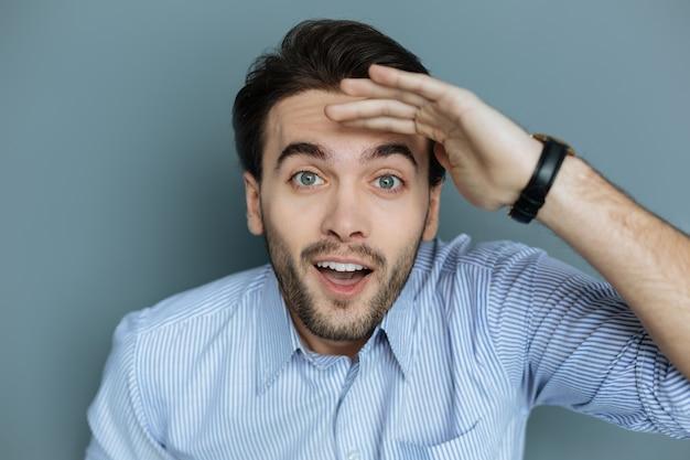 成功した検索。灰色の背景に立って、興奮しながら何かを探しているポジティブな幸せな喜びの男