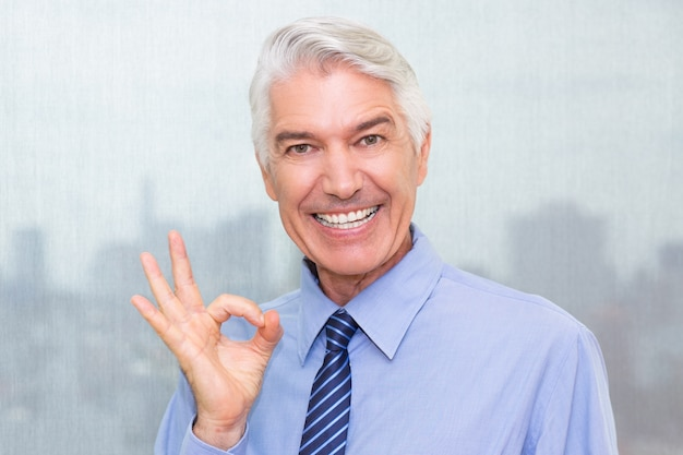 Successful senior businessman showing ok sign