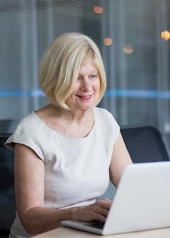 Successful senior businesswoman working at laptop