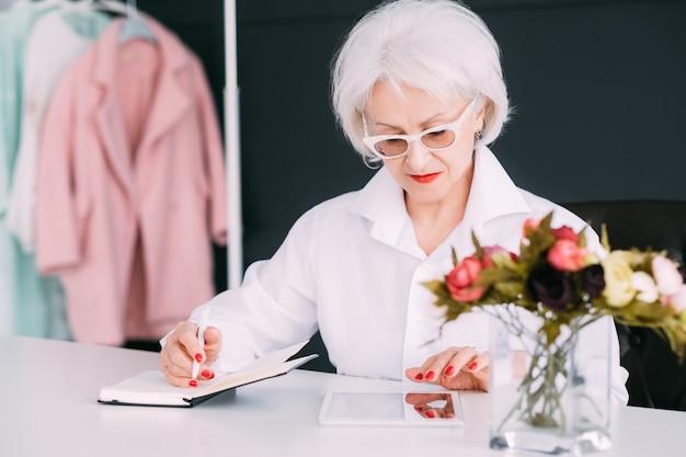 成功した年配の女性。ファッションブティックビジネス。タブレットの閲覧や手帳でのメモ作成に忙しい思いやりのあるおばあさん。